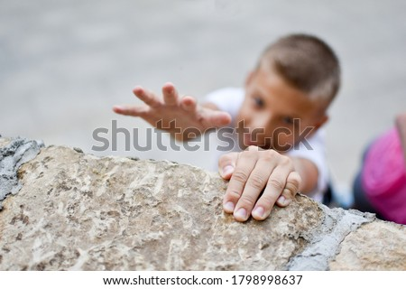 boy overcoming efforts. striving for a goal. conquering the top of the mountain. achieve a difficult goal. boy hanging on the wall. Photo stock ©