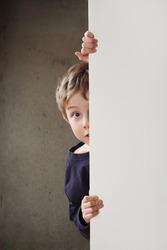 Boy Peeking around a wall