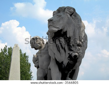 Boy petting the lion. Famous statue on the Bridge of Alexander III in Paris in France.