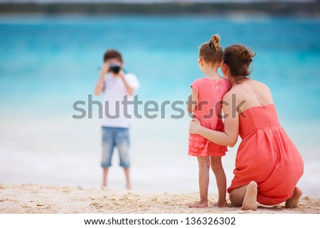 Boy photographing his mother and little sister at tropical beach