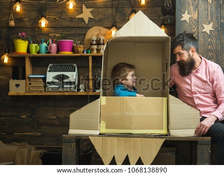 Boy play with dad, father, little cosmonaut sit in rocket made out of cardboard box. Kid happy sit in cardboard hand made rocket. Parenthood concept. Child cute boy play cosmonaut, astronaut.