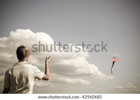 Boy play with fly kite. Photo in vintage yellow style.