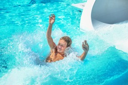 Boy playing at a waterpark pool going down a waterslide