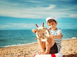 boy playing at the beach in sailor hat. Child with a steering wheel at sea