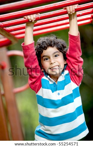 Boy playing at the monkey bars and smiling