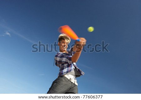 Boy playing cricket on beach