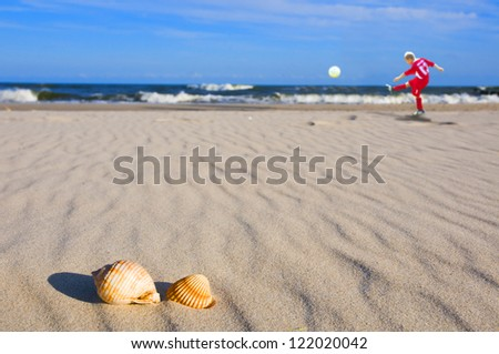 Boy playing football on the beach with shells