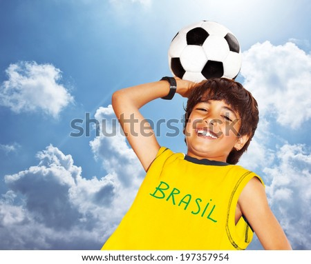 Boy playing football outdoor happy child teen goalkeeper enjoying sport game holding ball portrait of a preteen smiling and having fun kids activities little footballer over blue sky background