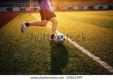 boy playing football with sunset