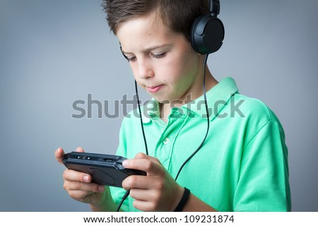 Boy playing game console against grey background