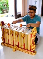 Boy playing gamelan Gender or Slenthem. Gamelan, traditional music instruments in Bali and Java, Indonesia.