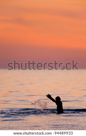 Boy playing in the ocean at sunset