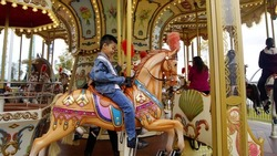 Boy playing merry go round horse