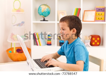 Boy playing or working on laptop computer in his room