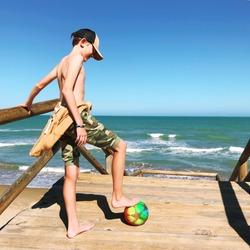 boy playing soccer on the beach. Beach football.