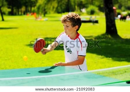 boy playing table tennis in the park