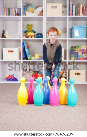 Boy playing ten pin bowling in play room