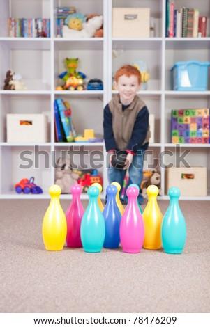 Boy playing ten pin bowling in play room