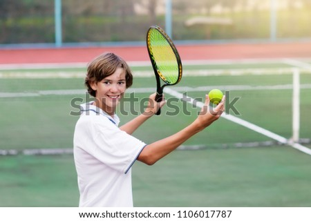 Boy playing tennis on outdoor court. Teenager with tennis racket and ball in sport club. Active exercise for kids. Summer activities for children. Training for young kid. Child learning to play. #1106017787