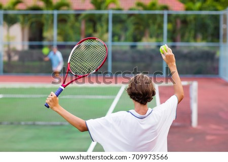 Boy playing tennis on outdoor court. Teenager with tennis racket and ball in sport club. Active exercise for kids. Summer activities for children. Training for young kid. Child learning to play. #709973566