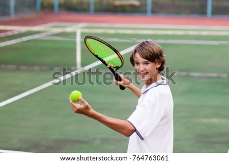Boy playing tennis on outdoor court. Teenager with tennis racket and ball in sport club. Active exercise for kids. Summer activities for children. Training for young kid. Child learning to play. #764763061