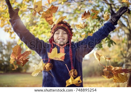 Boy playing with autumn leaves in the park
