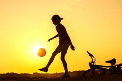 Boy playing with ball in nature, bicycle lies nearby, silhouette of playing child at sunset in countryside