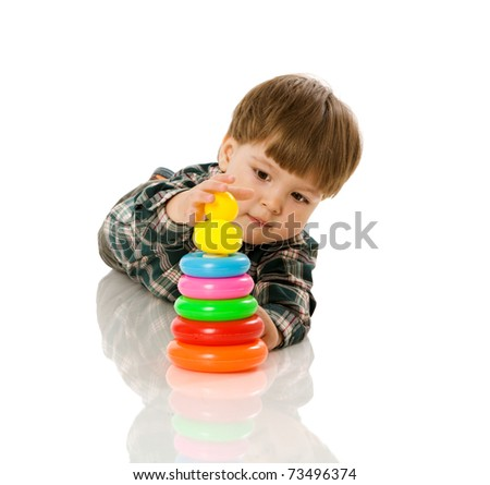 boy playing with colorful pyramid toy isolated on white
