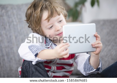 Boy playing with digital tablet, close up