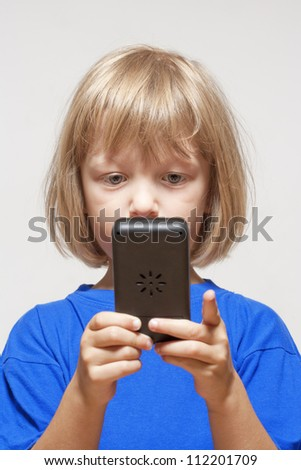 boy playing with handheld computer game - isolated on light gray