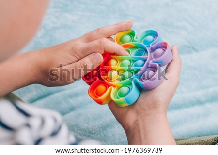 Boy playing with rainbow pop it fidget toy. Push bubble fidget sensory toy - washable and reusable silicon stress relief toy. Antistress toy for child with special needs. Mental health concept