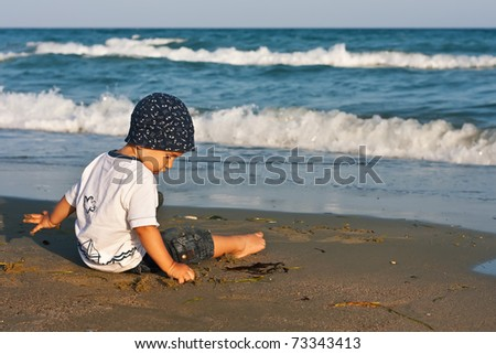 Boy playing with sand sitting on the beach