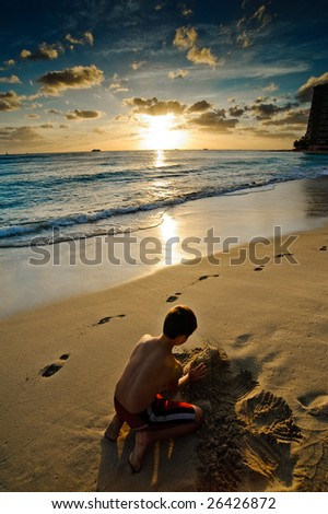 Boy playing with the sand at sunset