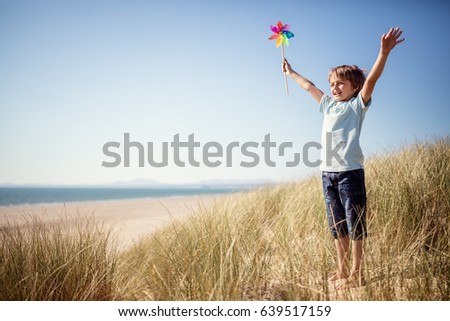 Boy playing with windmill in sand dunes at the beach on summer vacation concept for freedom or the environment