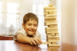 Boy playing wood tower game on wooden table. The high wooden tower of blocks falls.