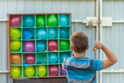 Boy plays balloon darts in the backyard - a box or set with colorful balloons for a carnival dart game, one ballon popped