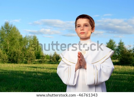 Boy portrait in his first holy communion, praying hands, clear conscience