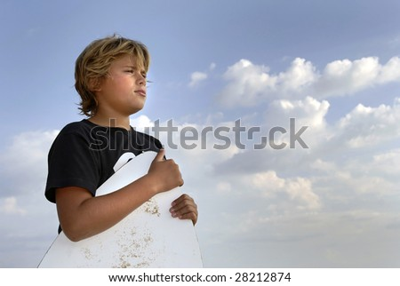 Boy posing in the beach with a skim-board