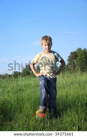 boy posing with football ball in the field