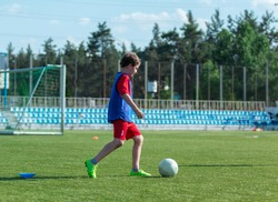 boy practices dribbling on the football field in good summer weather