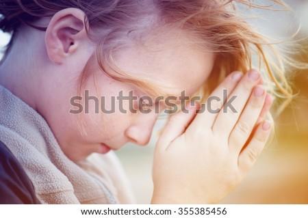 boy praying to God.