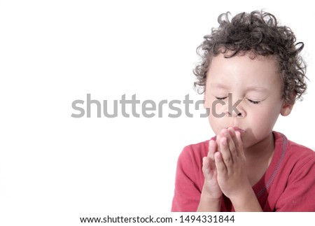 boy praying to God stock image with hands held together with closed eyes  #1494331844