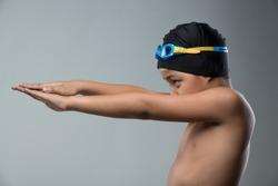 Boy prepare to swim freestyle on grey background