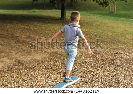 boy preschooler in shorts walks on horizontal sports game projectile on the playground in the park in summer, training coordination and body balance #1449162119