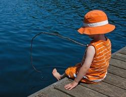 Boy pretending to fish off dock