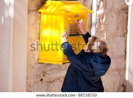 Boy puts letter into yellow postbox