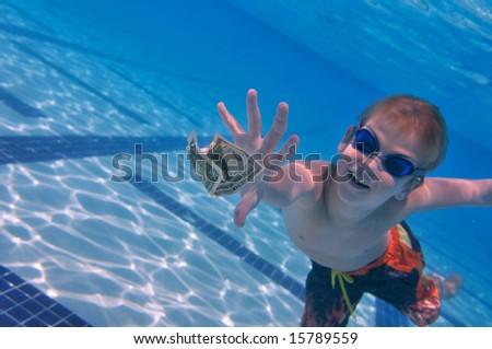 Boy reaching dollar bill swimming pool underwater shot for Swimmingpool billig