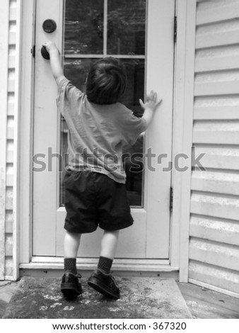 Boy reaching high, trying to open the door