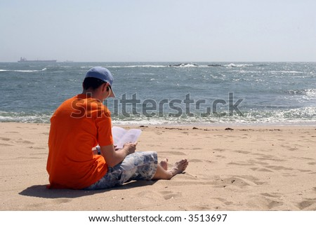 boy reading a book in the beach