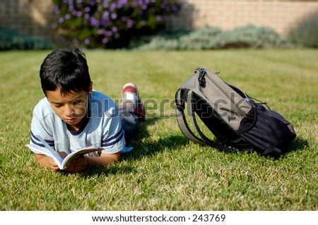 Boy reading a book lying on the grass.